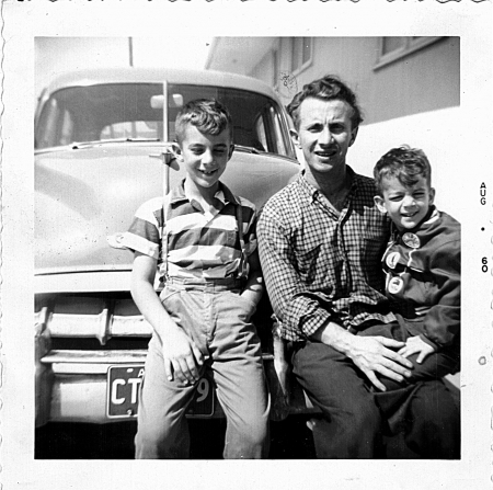 Black-and-white photograph of a man and his two boys, sitting on the front of a vintage car outdoors. The man and his sons smile at the camera.