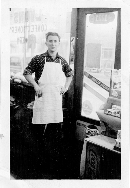 Black-and-white photograph of man standing inside a grocery store. He has his hands on his hips and wears a white apron, standing near the entrance door of the store. The window behind him is printed backwards with the words 'LYONS CONFECTIONARY STORE'.