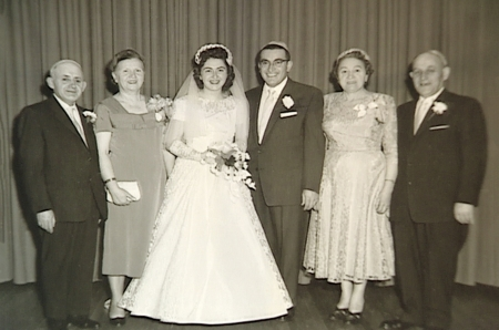 Black-and-white photograph of a group of six people, standing in a line and smiling at the camera. The couple in the middle appears to be celebrating their wedding day, with the woman dressed in a long white gown, veil, and holding a bouquet of flowers. The three men in the group wear suits, and the other two women wear dresses.