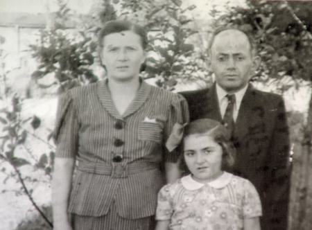 Black-and-white photograph of a man and woman with their young daughter, standing outdoors with trees in the background. The man wears a suit and the woman and young girl wear blouses.