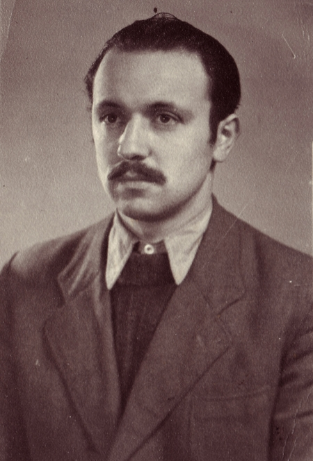 Sepia-toned portrait photograph of a man, pictured from the chest up, looking towards the left of the camera. He wears a suit and tie, and his hair is combed back. He has a moustache.