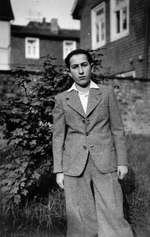 Black-and-white photograph of a young man standing outdoors in what appears to be a backyard, with a fence and shrub behind him. He wears a suit jacket and collared shirt, with his hair combed back.