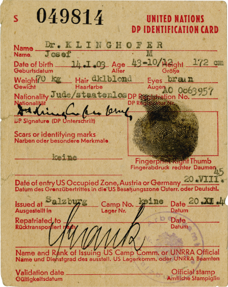 Copy of an aged yellow identity document. It contains red typed text with handwritten signatures, stamps, and a black fingerprint.