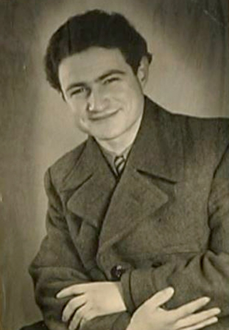 Black-and-white portrait photograph of a young man, pictured from the waist up, sitting with his arms crossed. He wears a jacket and smiles at the camera.