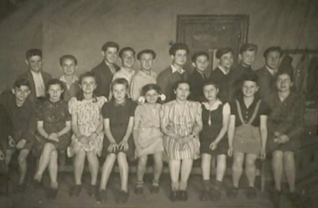 Black-and-white photograph of a classroom, grouped together in two rows of about 10-12 children each. The girls wear dresses, sitting in the front row and the boys stand in the back with collared shirts.