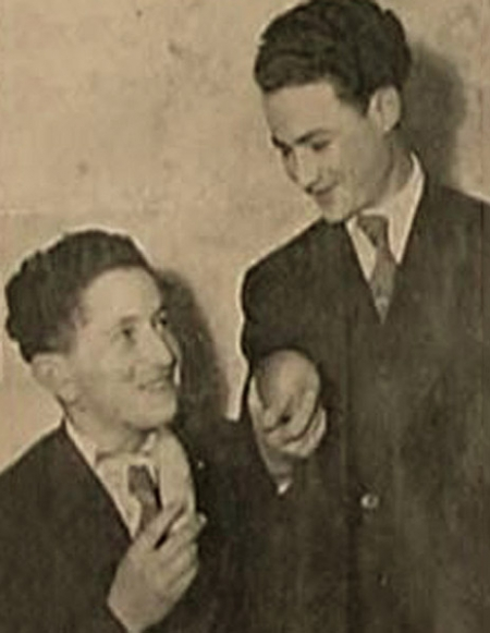 Black-and-white photograph of two young men, one of them sitting, smiling at each other. The two young men wear suits and are holding what appear to be pieces of fruit.