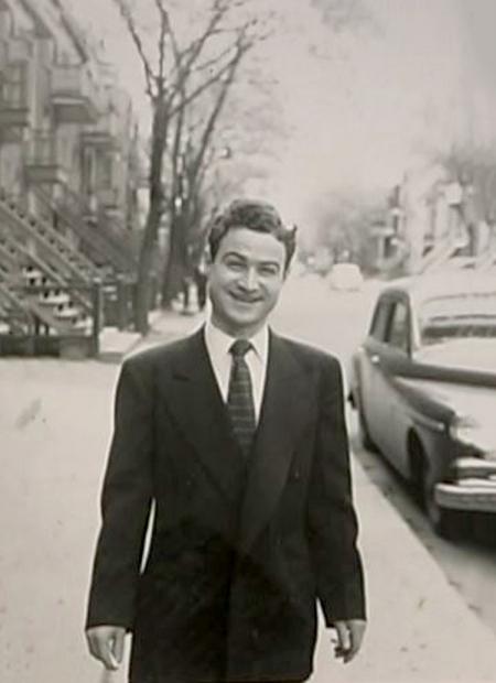 Photo en noir et blanc d'un homme se tenant sur un trottoir à l'extérieur, il porte un complet et sourit à la caméra. Il y a une voiture ancienne stationnée dans la rue à droite derrière lui ainsi que des arbres des arbres et des escaliers menant à des appartements.