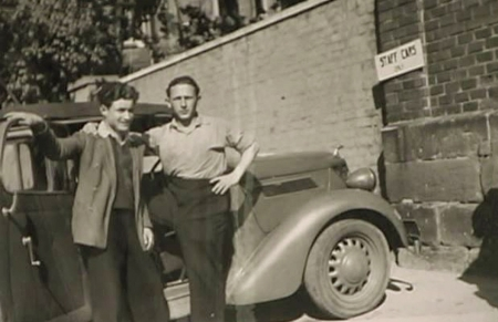 Black-and-white photograph of two young men standing together in front of a vintage car outdoors. One man has his arm around the other. A large brick wall is in the background.