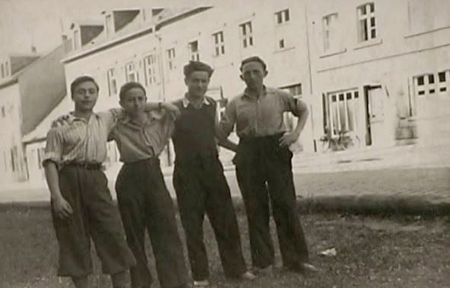 Black-and-white photograph of a group of four boys standing together arm-in-arm outdoors, in a shaded area, on a road. Across the street is a large building.