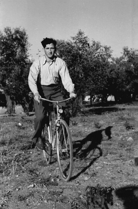 Black-and-white photograph of a young man riding a bicycle in a field. He wears dark trousers and a light collared shirt. There are trees in the background.
