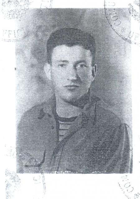 Photo d'identité en noir et blanc d'un jeune garçon, photographié de la poitrine. Il a des cheveux bruns foncés, porte une chemise à col par-dessus un t-shirt rayé.