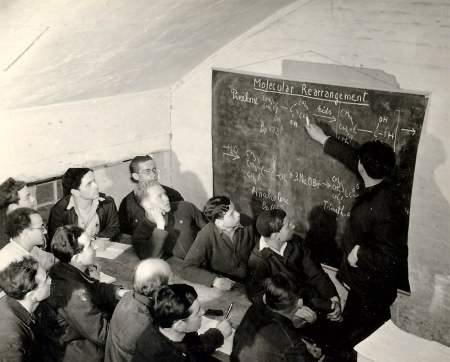 Black-and-white photograph of a group of about a dozen men looking at a chalk board. One of the men stands with a piece of chalk and points at an equation written on the board. The other men are sitting at a table, some taking notes with pen and paper.
