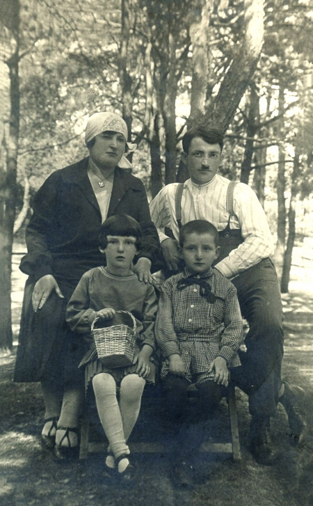 Black-and-white photograph of a family of four, grouped together for a photograph outdoors, surrounded by trees. The man and woman pose behind their two sitting children.