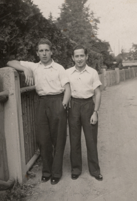 Black-and-white photograph of two young men standing together on a road, one of them leaning against a fence. They wear white collar, short sleeved shirts, and dark trousers.