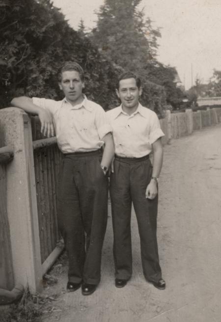 Photo en noir et blanc de deux jeunes hommes se tenant ensemble sur une route, l'un d'eux s'appuie sur une clôture. Ils portent des chemises blanches à manches courtes avec un col et des pantalons de couleur foncée.