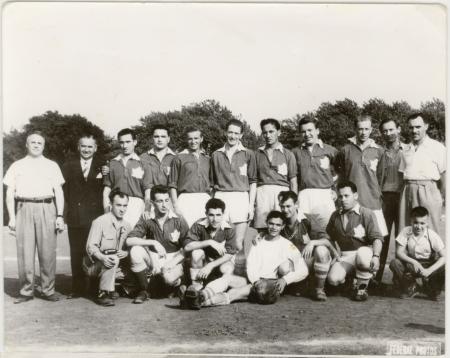 Photo en noir et blanc d'une équipe de soccer d'environ 15 jeunes hommes et quatre entraîneurs, répartis en deux rangées sur un terrain de soccer. Leur uniforme d'équipe présente un drapeau canadien sur leur poitrine.