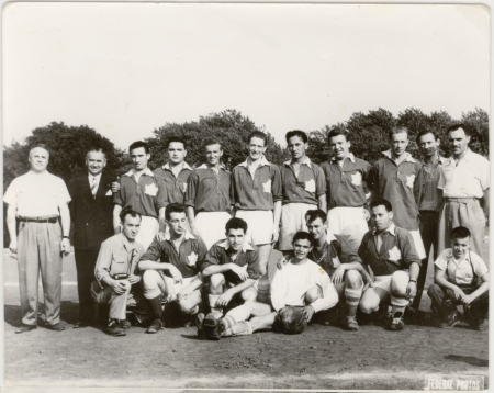 Black-and-white photograph of a soccer team of about 15 young men and 4 coaches, posing in two rows on a soccer field. Their soccer uniforms feature a Canadian flag on their chest.