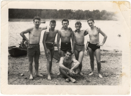 Black-and-white photograph of a group of 6 teenage boys standing arm-in-arm on a beach, with water in the background. The young men wear bathing suits, and one of them sits on the ground.