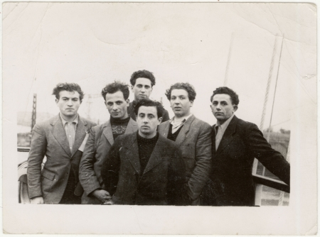 Black-and-white photograph of a group of 6 young men, standing together on the deck of a ship wearing coats.