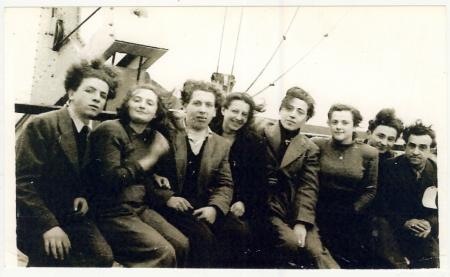 Photo d'un groupe de huit jeunes adultes, hommes et femmes, assis ensemble sur le pont  d'un navire.