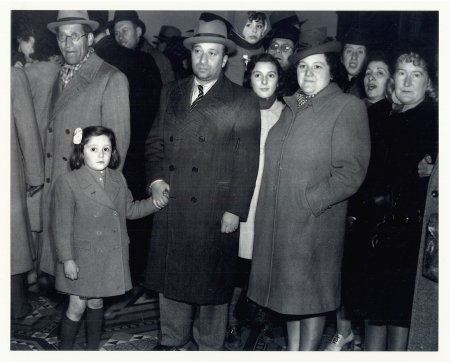Black-and-white photograph of a group of about a dozen people standing together and looking at the camera. They wear coats and hats. The man in the front row holds the hand of a young girl with a bow in her hair.