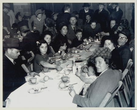 Black-and-white photograph of a large group of people sitting together at a long table, looking at the camera. The table is full of dishes and food. There are several more people in the room behind the table.