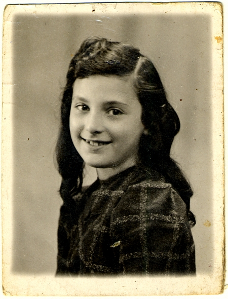Black-and-white portrait photograph of a young girl, turning her head to smile at the camera. She has long, wavy brown hair.