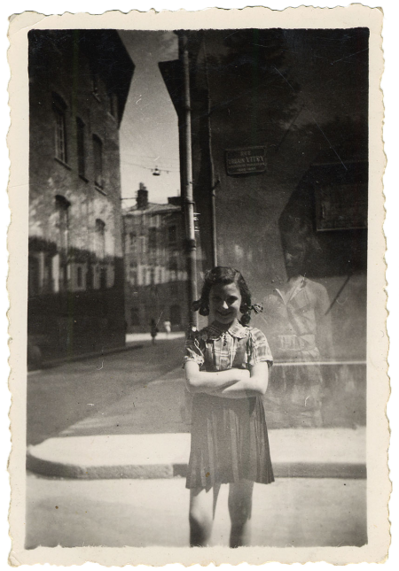 Black-and-white photograph of a young girl standing a street with her arms crossed, smiling at the camera. She stands near the corner of the street, with the road and sidewalk continuing in the background.
