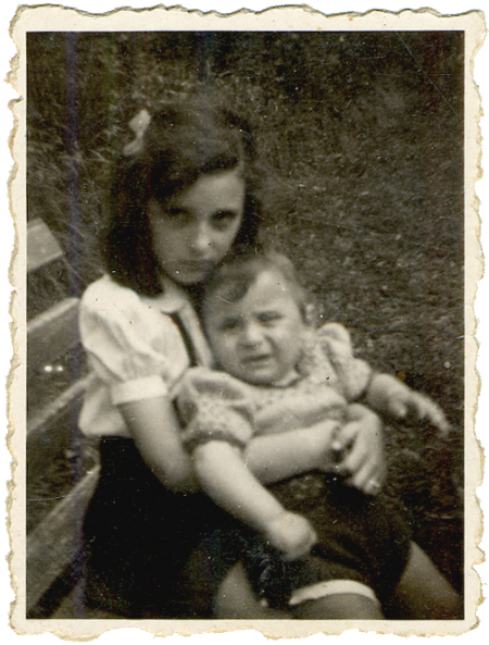 Black-and-white photograph of a girl sitting on a bench, holding a young toddler on her lap. The girl has a bow in her hair. The two siblings look at the camera, neither of them smiling.