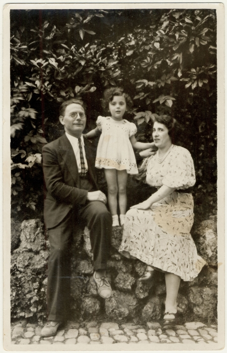 Black-and-white photograph of a man and woman sitting outdoors on a rock wall, with a young girl standing between on the wall between them, leaning on their shoulders for support. The woman and her daughter wear dresses, and the man is in a suit.