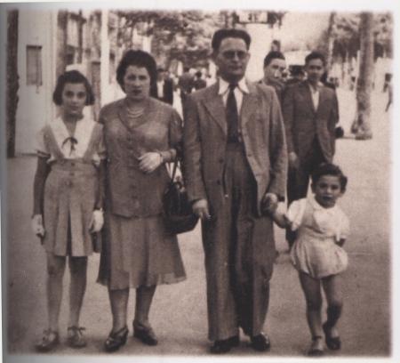 Photo de couleur sépia d'un homme et d'une femme, tenant les mains de leurs deux enfants se tenant de chaque côté d'eux. La famille de quatre est à l'extérieur sur une rue avec des personnes qui marchent en arrière-plan.