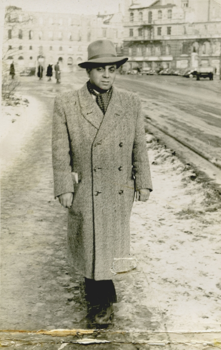 Black-and-white photograph of a man standing outdoors on a snowy sidewalk. The man wears a hat and coat, and there are buildings in the background.