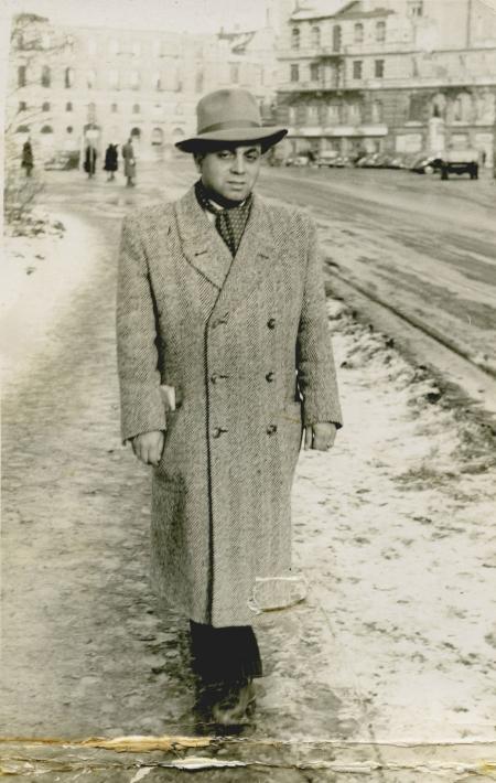 Photo en noir et blanc d'un homme se tenant à l'extérieur sur un trottoir enneigé. L'homme porte un chapeau et un manteau et il y a des édifices en arrière-plan.