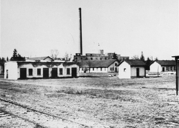 Black-and-white photograph of a field with one-storey barracks and a factory in the far background.