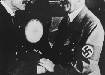 Black-and-white photograph of two men smiling and shaking hands. Both men have moustaches, and one man wears a lighter suit with a swastika badge on his arm.