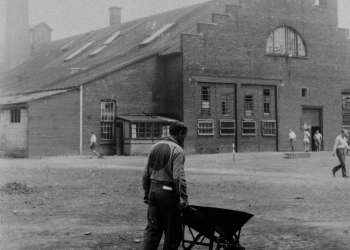 Black-and-white photograph of a man, with his back to the camera, pushing a wheelbarrow in a yard. There is a bench in the foreground, and a building in the far background. The man wears a uniform with a big circle on his back.