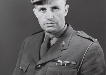 Black-and-white portrait photograph of a man, visible from his waist up, wearing a military suit.