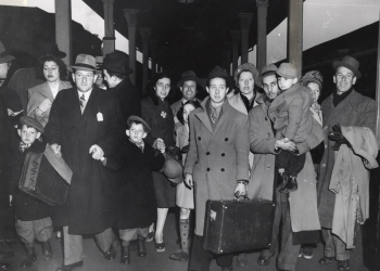 Black-and-white photograph a group of about 16 people walking towards the camera on a train platform. They are wearing jackets and some carrying suitcases. There are four young children in the group.