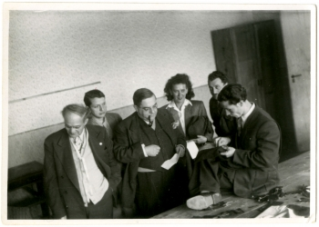 Black-and-white photograph of a group of six people, five men and one woman, standing in a room. One man is smoking a pipe and observing another man sitting on a table, hand sewing fabric.