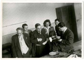 Photo en noir et blanc d'un groupe de six personnes, cinq hommes et une femme, se tenant debout dans une pièce. Un homme fume la pipe et observe un autre homme assis à une table qui cout un tissus à la main.