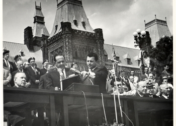 Black-and-white photograph of a man in a suit speaking into two microphones at a podium outdoors. He is surrounded by a group of people, some sitting, with a large building in the background.