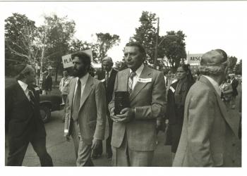 Photo en noir et blanc de quatre hommes menant une marche à l'extérieur. L'homme au centre transporte une boîte rectangulaire. Un groupe de personnes les suit à l'arrière.