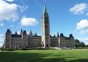 Color photo of the Canadian parliament central building with green grass at the front and a blue sky with a couple of clouds.