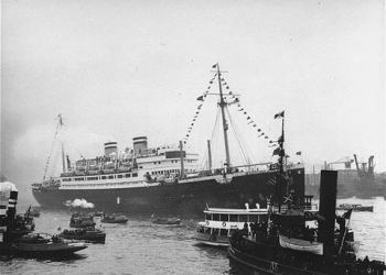 Black and white photograph of a passenger ship surrounded by smaller boats.