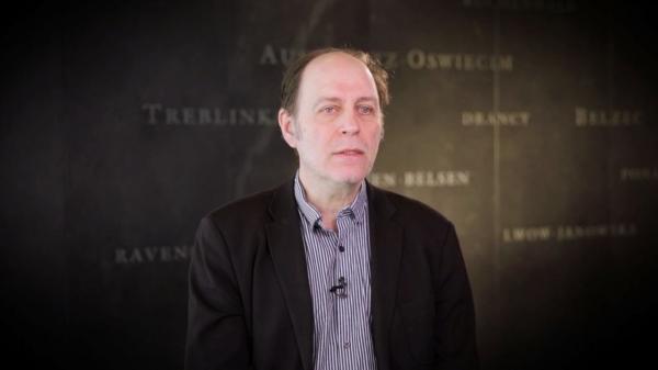 Capture d'écran de l'entrevue de Pierre Anctil. Il est assis devant un mur gris sur lequel est inscrit les noms de divers camps de concentration. Son visage et ses épaules sont visibles à la caméra.