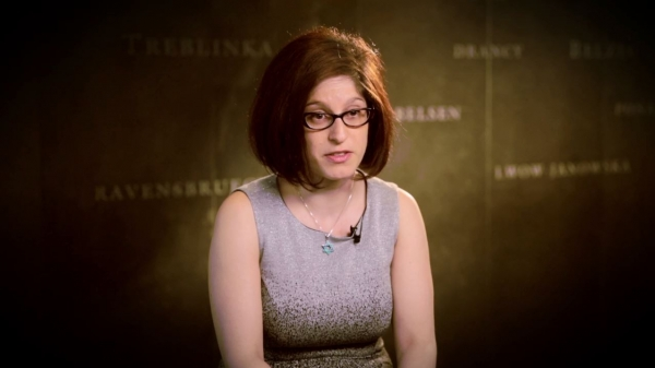 Screenshot from Adara Goldberg interview. She is sitting in front of a grey wall with various camps names written on it. Her face and shoulders are visible at the camera.