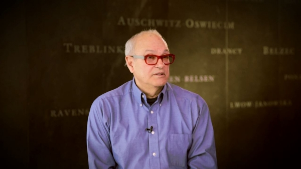 Screenshot from Harold Troper interview. He is sitting in front of a grey wall with various camps names written on it. His face and shoulders are visible at the camera.