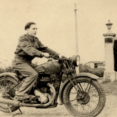 Black-and-white photograph of a young man posing on the back of a motorcycle, looking forwards towards the right of the camera. There is a hedge behind him and a building in the distant background.