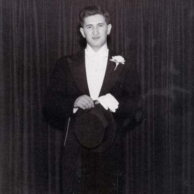 Black-and-white photograph of a young man standing in a tuxedo, in front of a dark curtain.