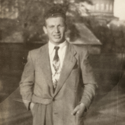 Black-and-white photograph of a man wearing a suit and tie, standing outdoors on a field. A building tower is visible in the background.